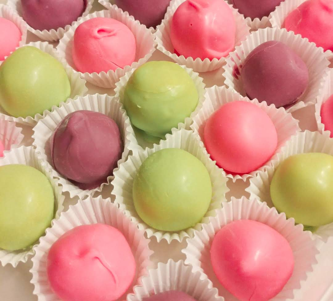 Cake balls dipped in green, purple, and pink chocolate