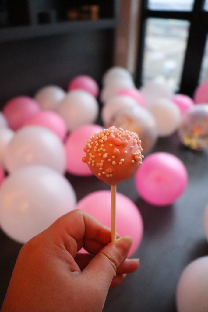 Holding a pink cake pop behind pink and white balloons.